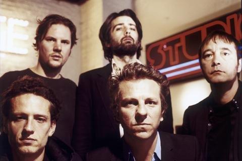 Tom Barman (keskellä edessä) ja dEUS.