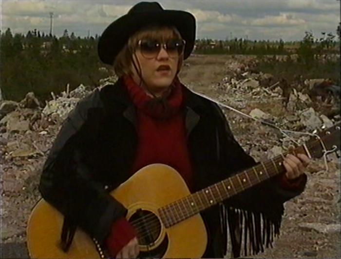 Kuvateksti: Saara Suvanto esittämässä Kissat ja koirat ja linnutkin -kappaletta vuonna 1990. (Lähde: YLE TV1 Mediakomppanian henkilökuva samalta vuodelta.)